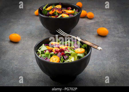 Bowl of mixed green salad with red cabbage, kumquat and pomegranate seeds - Stock Photo