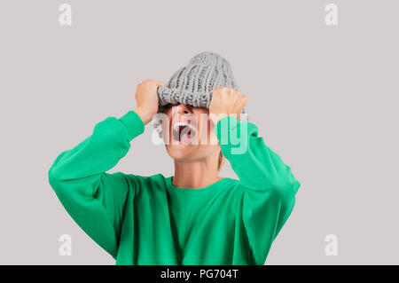 Furious. Emotional angry woman is pulling wool hat over her eyes on gray background - Stock Photo