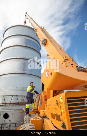 Worker standing on a crane on construction site using walkie talkie - Stock Photo