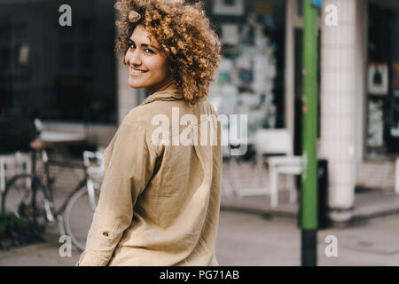 Woman in the city, walking away, smiling - Stock Photo