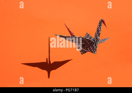 Origami crane, orange background, shadow, copy space - Stock Photo