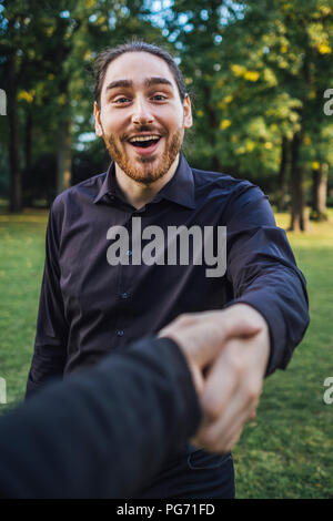 Young businessman greeting business partner in a park, negotiating business transactions - Stock Photo
