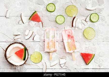 Homemade watermelon coconut ice lollies with lime and cucumber slices, fresh coconut and watermelon pieces on ice cubes - Stock Photo