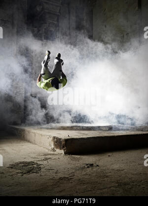 Man jumping in dust cloud during freerunning exercise - Stock Photo
