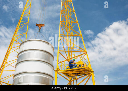 Construction worker working on crane next to tank - Stock Photo