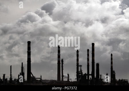 Silhouette of a big oil refinery against cloudy sky in a winter day - Stock Photo
