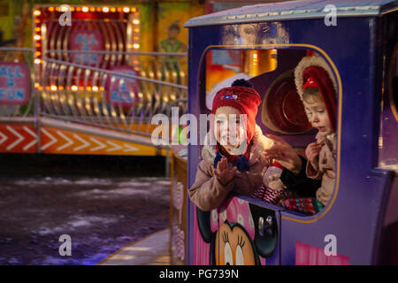 Young girls on a mini mouse train ride. - Stock Photo