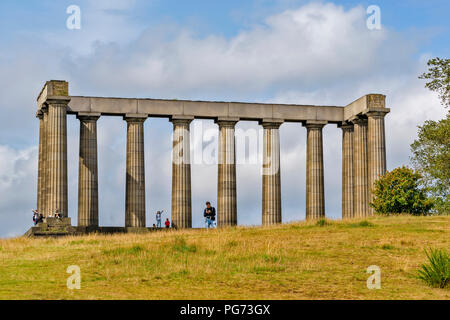 EDINBURGH SCOTLAND CALTON HILL THE NATIONAL MONUMENT OR ACROPOLIS AND TOURISTS IN SUMMER - Stock Photo