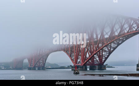 FORTH RAILWAY BRIDGE OVER THE FIRTH OF FORTH SCOTLAND EMERGING FROM EARLY MORNING MIST - Stock Photo
