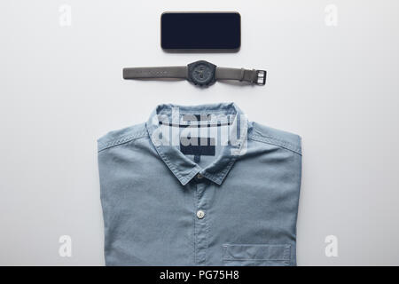 top view of shirt, smartphone and wristwatch isolated on white - Stock Photo