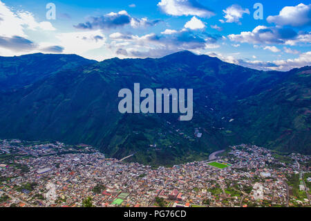 Above view of the city of Banos, Ecuador, view from the bellavista observation point, and huge muntain behind in cloudy day. - Stock Photo