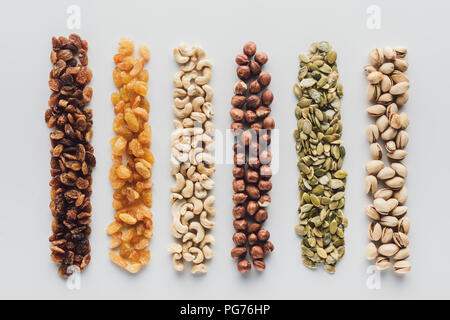Assorted delicious nuts and raisins isolated on white background - Stock Photo