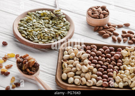 Assorted delicious nuts and raisins in wooden plates and spoon - Stock Photo