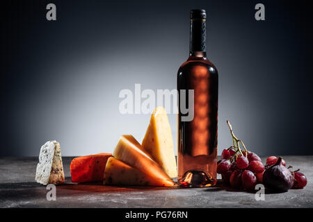bottle of red wine, different types of cheeses and grapes on grey - Stock Photo