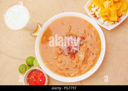 Above view of traditional Ecuadorian food called Encebollado, fish stew and ring onions inside, served with popcorn, chifles, lemon and glass of beer with red sauce inside of bowl - Stock Photo
