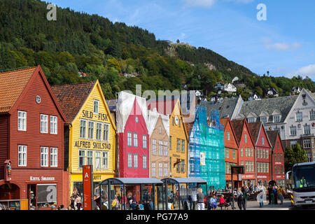 The port area of Bryggen in Bergen harbor, west Norway. Some of the buildings are being renovated. Mount Floyen in the background. - Stock Photo