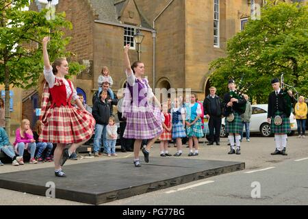 Young Scottish Highland dancers performing for tourist in the main square in Dornoch, Sutherland, Scotland, UK - Stock Photo