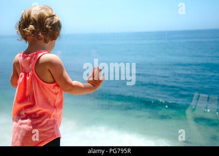 little girl looking out to the ocean and wanting to go play in the water. - Stock Photo