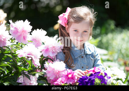 Belarus, Gomel, May 29, 2018. The central kindergarten. Open day.A six-year-old girl sits next to a hydrangea bush - Stock Photo