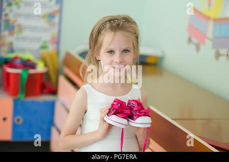 Belarus, Gomel, May 30, 2018. The central kindergarten. Open day.Beautiful preschool girl with toy sneakers - Stock Photo