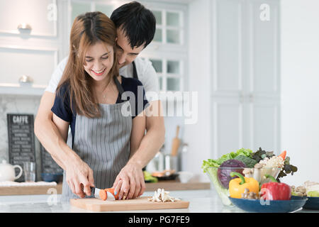 Young beautiful couple in kitchen. Family of two preparing food. Couple making delicious salad. Cooking hobby lifestyle concept. - Stock Photo