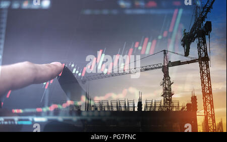 Investment in real estate business. Double exposure, finger pointing on raising graph and building construction - Stock Photo