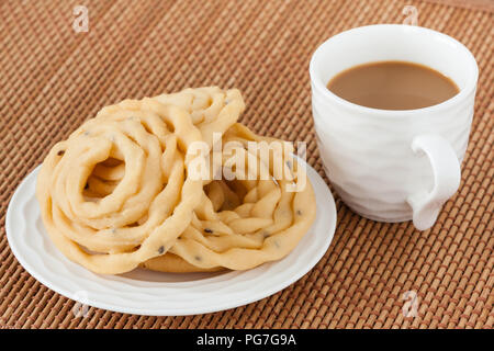 Indian murukku snack with coffee - A closeup of traditional deep fried Indian snack murukku on a plate served with coffee. - Stock Photo