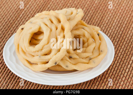 Indian murukku snack - A macro closeup of traditional deep fried Indian snack murukku on a plate. - Stock Photo