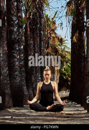 Young woman in black sportswear sitting in lotus position and meditating outdoors. Woman in early gestation. Pre natal exercising, healthy lifestyle.  - Stock Photo