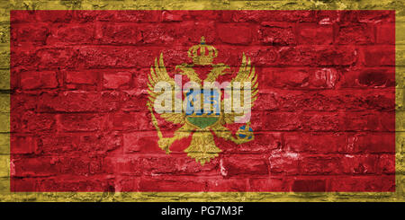 Flag of Montenegro over an old brick wall background, surface - Stock Photo