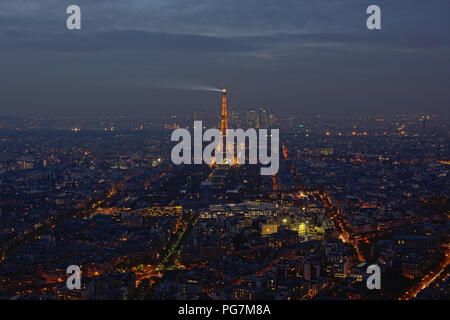 Cityscape of Paris at night, with Eiffel tower and skyscrapers of La Defense business district behind. - Stock Photo