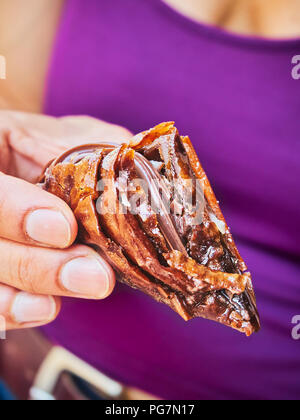 A female hand holding a Chocolate Trigona Panoramatos, typical Greek phyllo sweet. - Stock Photo