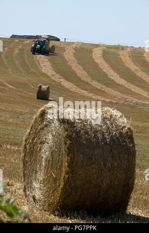 A tractor and baling machine xollecting and baiing hay near Najac, Aveyron, Occitanie, France, Europe - Stock Photo