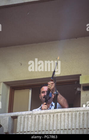 Joyous Iraqi firing gun  from his apartment block balcony, in celebration of President Saddam Hussein's overwhelming victory in single candidate election with a single question, 'Do you approve of Saddam Hussein as president of the Republic?' yes or no referendum, of which he won 99.6%. - Stock Photo