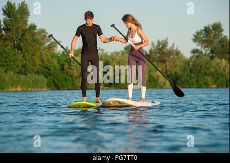 Happiness boy and girl on sup surf swimming at the river. Couple practicing - Stock Photo
