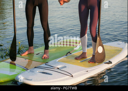 Happiness boy and girl on sup surf swimming at the river. Legs - Stock Photo