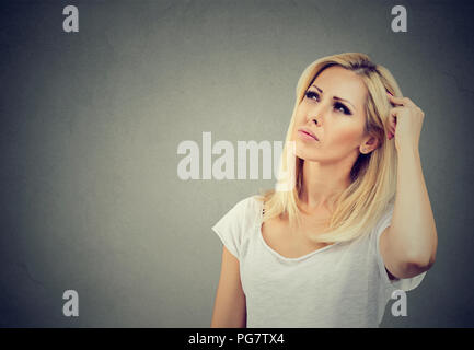 Young thoughtful woman looking up in mindfulness having memory problem on gray background - Stock Photo