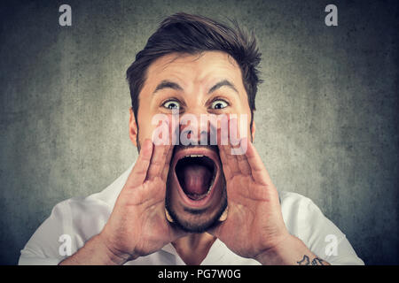 Closeup portrait of upset, angry man with hands close to wide opened mouth yelling, isolated on gray wall background. Negative emotion, feelings. - Stock Photo