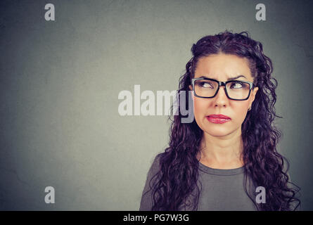 Closeup of a thoughtful young woman in glasses looking up contemplating on future plans has some doubts - Stock Photo