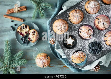 Blueberry muffins with sugar icing in a baking tray with Christmas decorations around, flat lay, view from above - Stock Photo