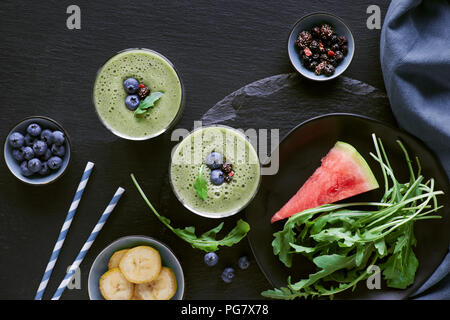 Green rucola, banana and watermelon smoothie in glass jars on dark slate background. Detox liquid food with ingredients and toppings - Stock Photo