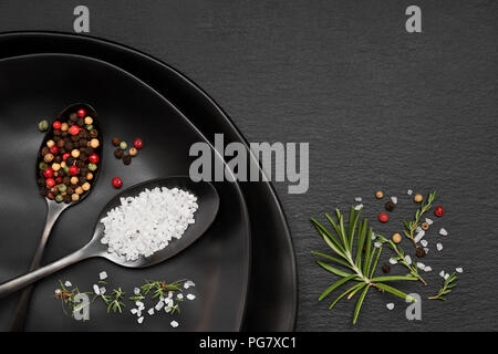 Salt in mixed pepper in dark spoons on black ceramic plates on slate stone with rosemary and thyme herbs - Stock Photo