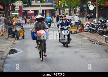 A woman wearing traditional conical straw hat rides a bicycle in the UNESCO protected town of Hoi An, Central Vietnam. - Stock Photo