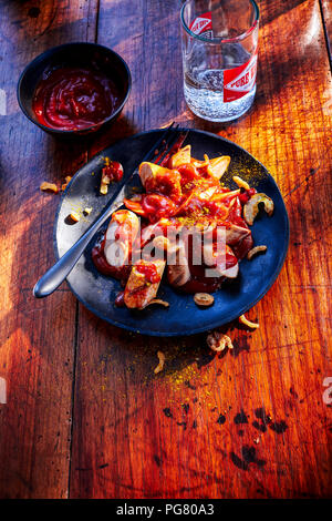 Currywurst with barbecue sauce on plate - Stock Photo