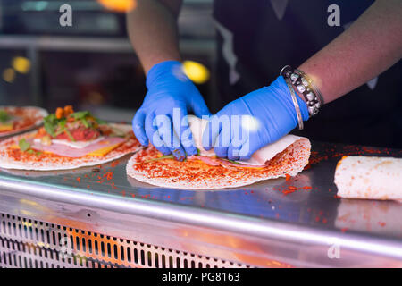 Woman in market stall filling tortilla wraps - Stock Photo