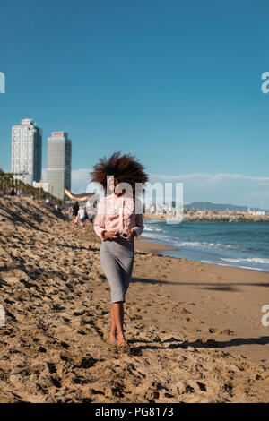 Young woman with afro hairdo walking on the beach - Stock Photo