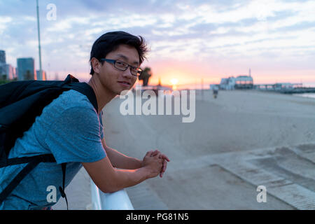 Young Chinese man with backpack looking at beach - Stock Photo