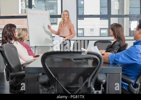 Businesswoman leading a presentation on a meeting in conference room - Stock Photo