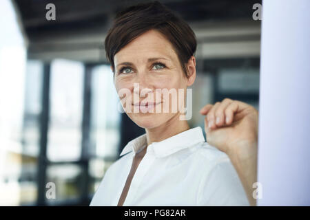 Portrait of smiling businesswoman in office looking out of window - Stock Photo