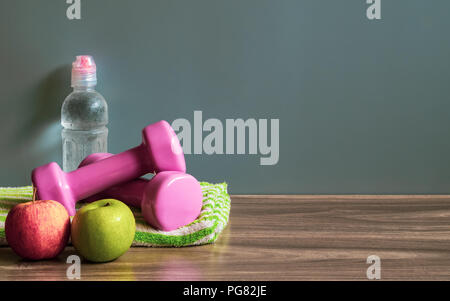 Healthy and active lifestyle background concept. Green and Red Apples, Dumbbells and bottle of water on wood floor with copy space. - Stock Photo